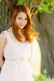 Portrait of beautiful young woman near tree on the wonderful par. K background Royalty Free Stock Image