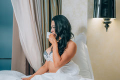 Portrait of beautiful young woman in nightwear holding coffee cup on bed. Royalty Free Stock Photo