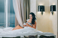 Portrait of beautiful young woman in nightwear holding coffee cup on bed. Stock Photos
