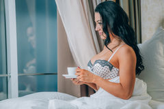 Portrait of beautiful young woman in nightwear holding coffee cup on bed. Stock Image