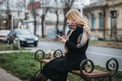 Free Portrait Beautiful Young Woman On Bench In Urban Background Looking Phone Royalty Free Stock Images - 141450759