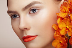 Portrait of beautiful young woman with orchid. Brunette woman with luxury makeup. Perfect skin. Eyelashes. Cosmetic eyeshadow. Orange flowers Stock Photography