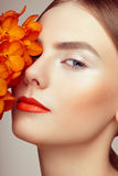 Portrait of beautiful young woman with orchid. Brunette woman with luxury makeup. Perfect skin. Eyelashes. Cosmetic eyeshadow. Orange flowers Stock Image