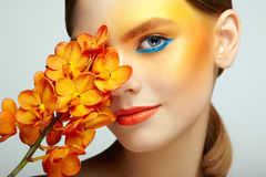 Portrait of beautiful young woman with orchid. Brunette woman with luxury makeup. Perfect skin. Eyelashes. Cosmetic eyeshadow. Orange flowers Royalty Free Stock Photo