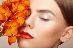 Portrait of beautiful young woman with orchid. Brunette woman with luxury makeup. Perfect skin. Eyelashes. Cosmetic eyeshadow. Orange flowers Royalty Free Stock Photography