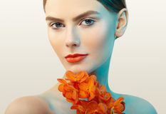 Portrait of beautiful young woman with orchid. Brunette woman with luxury makeup. Perfect skin. Eyelashes. Cosmetic eyeshadow. Orange flowers Royalty Free Stock Image