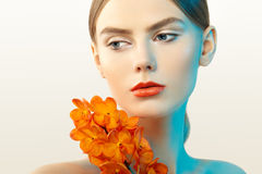 Portrait of beautiful young woman with orchid. Brunette woman with luxury makeup. Perfect skin. Eyelashes. Cosmetic eyeshadow. Orange flowers Stock Images