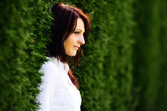 Portrait of a beautiful young woman outdoors. Shot agianst tall green bushes Stock Images