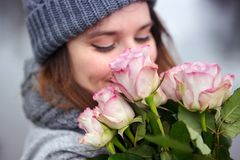 Young woman outdoors with bouquet of pink roses. Portrait of beautiful young woman outdoors with bouquet of pink roses Stock Photo