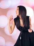 Portrait of beautiful young woman with perfume bottle. Royalty Free Stock Photos
