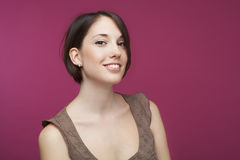 Portrait of a beautiful young woman on pink background. Stock Photos