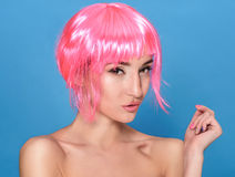 Portrait of beautiful young woman with pink hair on a blue background Royalty Free Stock Photos