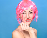Portrait of beautiful young woman with pink hair on a blue background Stock Image