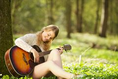 Portrait of a beautiful young woman playing guitar outdoors Stock Photos