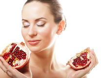Portrait of a beautiful young woman with a pomegranate. stock photo
