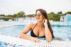 Portrait of beautiful young woman in the poolside of a resort swimming pool during summer holiday royalty free stock image
