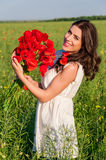 Portrait of beautiful young woman with poppies in the field with a poppies bouquet. Royalty Free Stock Image