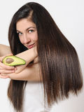 Portrait of a beautiful young woman posing with an avocado over white isolated background. Studio portrait of a beautiful young woman posing with an avocado over stock image