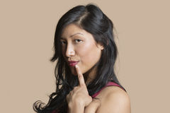 Portrait of a beautiful young woman posing with finger on lip over colored background Stock Photo