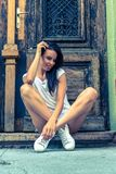 Portrait of a beautiful young woman posing in front of a door Stock Photos