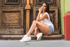Portrait of a beautiful young woman posing in front of a door Royalty Free Stock Photos
