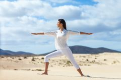 Portrait of beautiful young woman practicing yoga in desert stock photos
