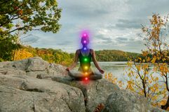 Portrait of beautiful young woman practicing yoga. Woman is meditating with glowing seven chakras on stone outdoor. Woman is practicing yoga on the lake royalty free stock photos