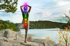 Portrait of beautiful young woman practicing yoga. Woman is meditating with glowing seven chakras on stone outdoors. Beautiful  woman is practicing yoga on the royalty free stock images