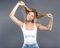 Beautiful young woman pulling her hair over gray background. royalty free stock images