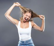 Beautiful young woman pulling her hair over gray background. royalty free stock photo