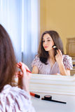 Portrait of beautiful young woman putting on makeup royalty free stock photography