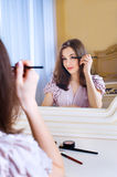 Portrait of beautiful young woman putting on makeup stock photography