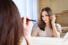 Portrait of beautiful young woman putting mascara stock images