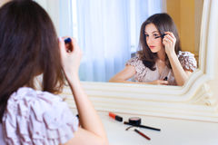 Portrait of  beautiful young woman putting mascara Royalty Free Stock Photos
