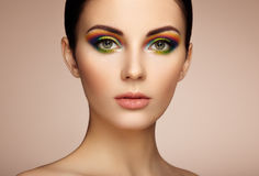 Portrait of beautiful young woman with rainbow make-up stock photography