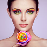 Portrait of beautiful young woman with rainbow rose stock photo