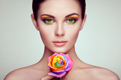 Portrait of beautiful young woman with rainbow rose Royalty Free Stock Photo