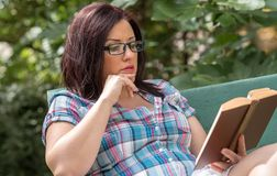 Portrait of beautiful young woman reading a book on a bench in park. In summer Royalty Free Stock Photos