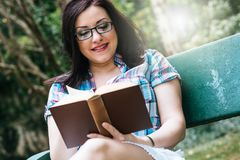 Portrait of beautiful young woman reading a book on a bench in park, light effect. Portrait of beautiful young woman reading a book on a bench in park in summer Royalty Free Stock Photos