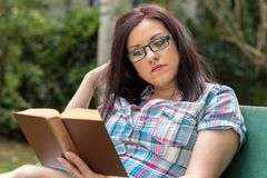 Portrait of beautiful young woman reading a book on a bench in park. In summer Stock Image