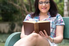 Portrait of beautiful young woman reading a book on a bench in park. In summer Royalty Free Stock Photography