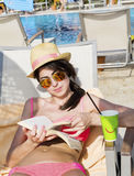 Portrait of beautiful young woman reading a book on the pool. Reading a book on the beach .summer sea vacation Stock Photos