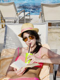 Portrait of beautiful young woman reading a book on the pool. Reading a book on the beach .summer sea vacation Royalty Free Stock Images