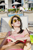 Portrait of beautiful young woman reading a book on the pool. Reading a book on the beach .summer sea vacation Stock Photo