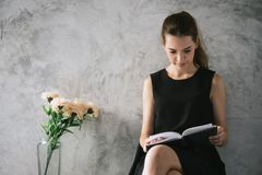 Portrait of a beautiful young woman reading book relaxing in living room. Vintage effect style pictures Royalty Free Stock Images