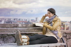 Portrait of beautiful young woman reading a book sitting  on a bench Stock Photo