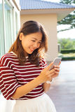 Portrait of beautiful young woman reading message in smart phone Royalty Free Stock Photo