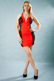 Portrait of a beautiful young woman in red dress. On blue background Royalty Free Stock Images