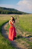 Portrait of a beautiful young woman in a red dress on a background of sky and grass in summer. Beautiful young happy woman in long red dress dreams in green Stock Photos
