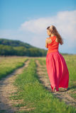 Portrait of a beautiful young woman in a red dress on a background of sky and grass in summer. Beautiful young happy woman in long red dress dreams in green Stock Images